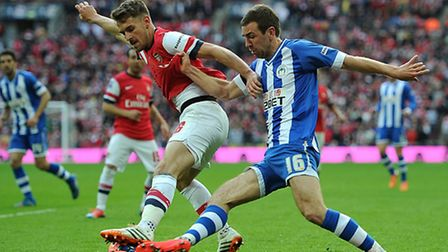 Arsenal's Aaron Ramsey (left) and Wigan Athletic's James McArthur battle for the ball. Picture: PA