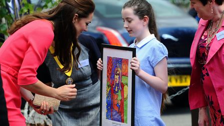 LONDON, ENGLAND - JULY 01: Catherine, Duchess of Cambridge is presented by artwork by a pupil after