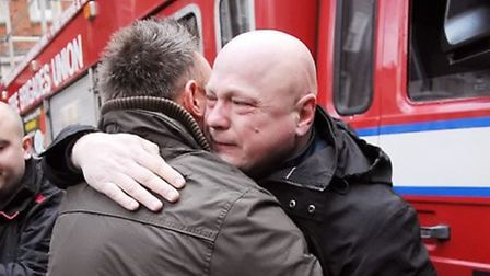 Tearful firefighter Alex Badcock is consoled by a colleague in January