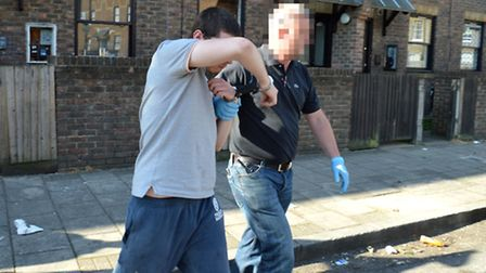 The 21-year-old suspect is led away by police after the raid.