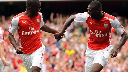 Arsenal's Joel Campbell (L) celebrates with team mate Yaya Sanogo. Picture: Andrew Matthews/PA Wire