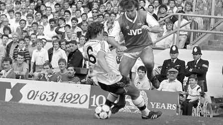 Arsenal's Charlie Nicholas (r) tries to slip the ball past the tackle from Manchester United's Kevin