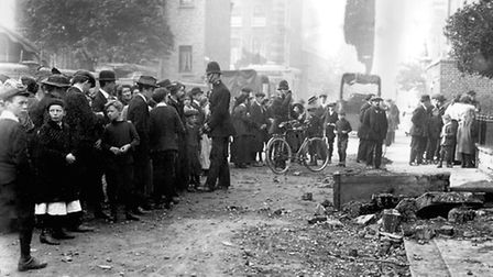 A crowd gather outside a bombed house.