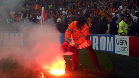 A steward pours water on a flare on the pitch - Pic John Walton
