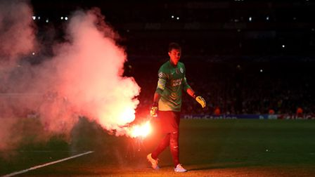 Galatasaray's Fernando Muslera removes a flare thrown onto the pitch - Pic John Walton