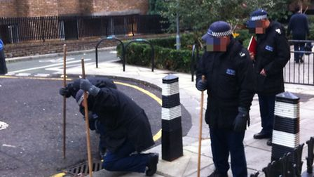 Officers from the Met's POLSAR unit search for disgarded weapons in Ampton Street
