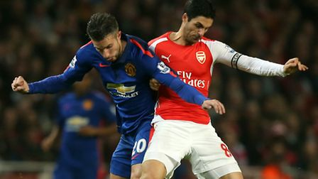 Manchester United's Robin Van Persie (left) and Arsenal's Mikel Arteta (right) battle for the ball