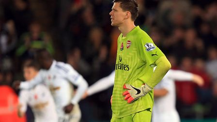 Arsenal's Wojciech Szczesny stands dejected after Swansea City's Bafetimbi Gomis scores his side's s