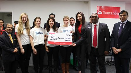Staff presenting their cheque to Orbis