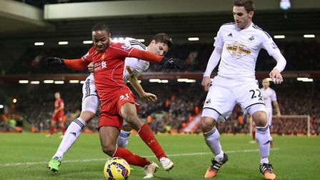 Liverpool's Raheem Sterling battles for the ball with Swansea City's Federico Fernandez and Swansea