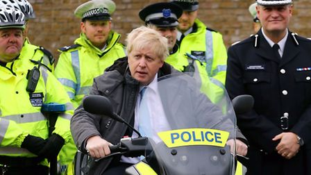 Mayor of London Boris Johnson sits on a police motorcycle as he meets with officers from the Metropo
