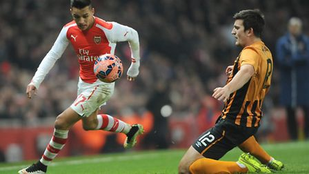 Arsenal's Alexis Sanchez (left) gets past Hull City's Harry Maguire during the FA Cup, Third Round m