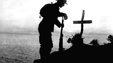 A British soldier paying his respects at the grave of a comrade. Picture: PA