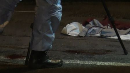 Bloods stains at the feet of forensics team member in Roman Way