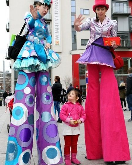 Stilt walkers with a bemused youngster