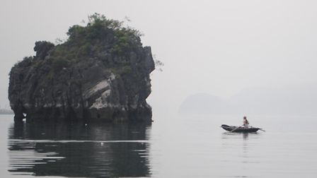 A lonely boater rows amid the natural monuments