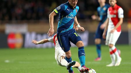 Arsenal's Mesut Ozil is challenged from behind in AS Monaco v Arsenal. Picture: PA/Mike Egerton