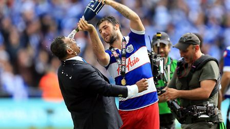 Queens Park Rangers' Charlie Austin celebrates by pouring champagne over chairman Tony Fernandes fol