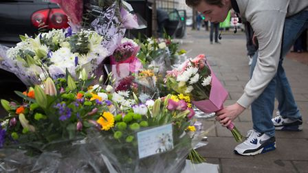 Floral tributes are left on Caledonian Road where teenage cyclist Alan Cartwright was stabbed to dea