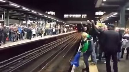 The football fans chant at each other from opposite platforms