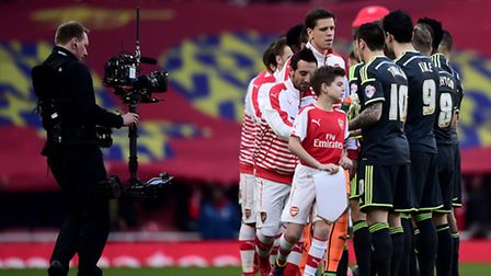 Arsenal and Middlesborough players shake hands whilst being filmed by a Television camera