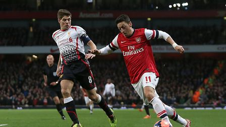 Arsenal's Mesut Ozil (right) and Liverpool's Steven Gerrard (left) battle for the ball. Picture: Joh
