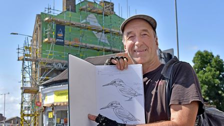ATM poses in front of the mural in its early stages with his original sketches. Photo Mick Howes