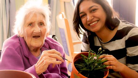 Project Leader Rida Khan helps resident at Bridgeside Lodge Care Centre to paint a flower pot