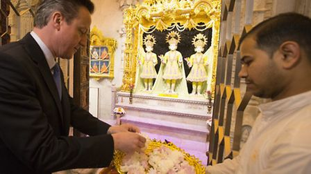 David Cameron offering flower petals to the deities as a mark of respect at Neasden Temple