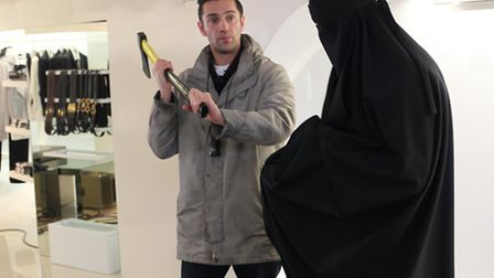 Reg shows a burkha clad cast member how he'd like him to wield his axe