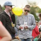 Festivalgoers inhale gas from a balloon