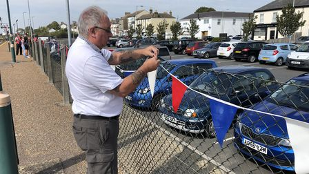 Lowestoft Central Project Volunteer Tim Miller helps decorate the station with bunting prior to the