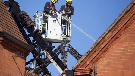 Fire crews were still working to contain 'hot spots' in the charred roof this morning (Pic Credit: A