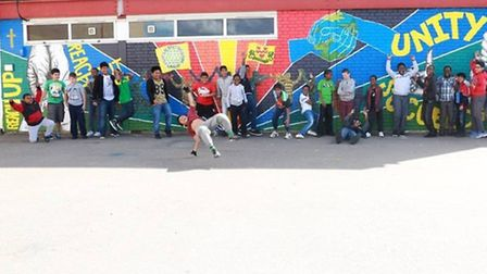 Students gather in front of their vibrant mural at Newman Catholic college (Pic: Angela Blake)