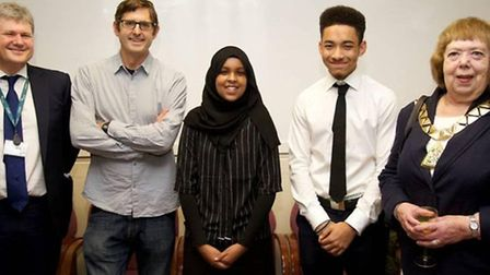 Top-scoring students James Simkins and Omaima Ali celebrate with Louis Theroux, head teacher Gerard