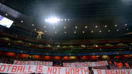 Bayern fans protest banners in the Emirates away section as they refused to watch the first five mi