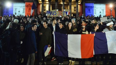 People display the French Tricolor during a vigil at Trafalgar Square, in London, as London stands i