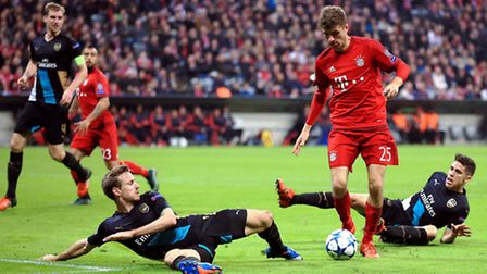 Bayern Munich's Thomas Muller evades the challenges of Gabriel (right) and Nacho Monreal