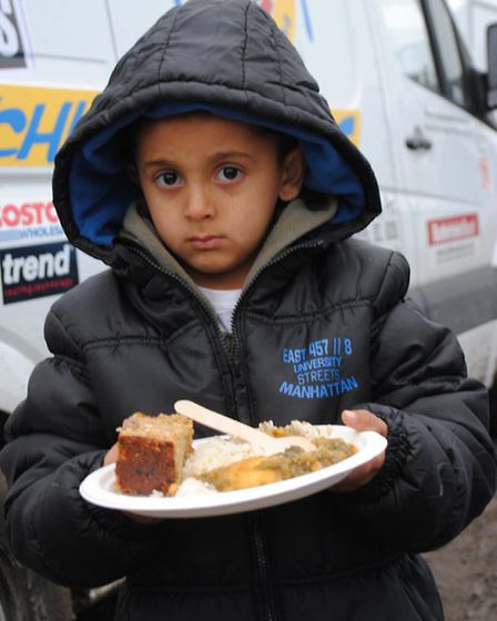 A child holds a meal provided by the Food For All team at the 'Jungle' migrant camp in Calais