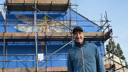 ATM poses infront of the Norfolk hawker dragonfly mural, his fourth of five in the town. Photo: Matt