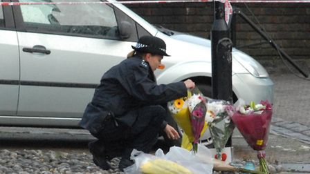 An officer arranges flowers at the stabbing scene in Yoke Close