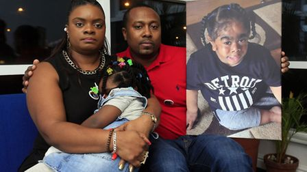 Pat and Norris Martin with their daughter Tashana-Rae, five, and a photo of their late son TJ, six (