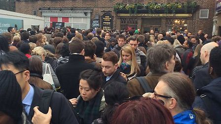 Commuters packed outside Highbury & Islington Station this morning after it was evacuated. Picture: