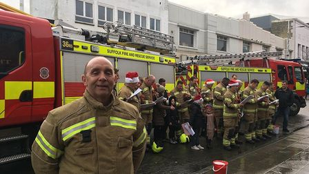 Group commander Paul Field posing in front of the rest of the firefighters at their carols. Photo: M
