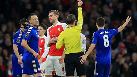 Arsenal's Per Mertesacker is shown a red card against Chelsea by referee Mark Clattenburg