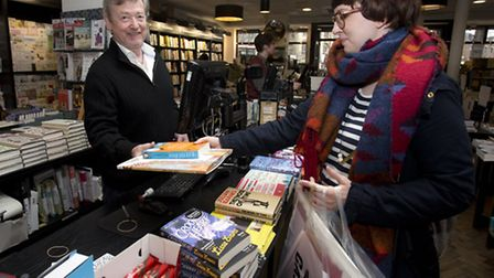 Shop assistant Allan Newton sells a book to a customer at the Waterstones at Islington Green