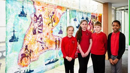 Students from Tufnell Park Primary School with exhibition artwork in the background