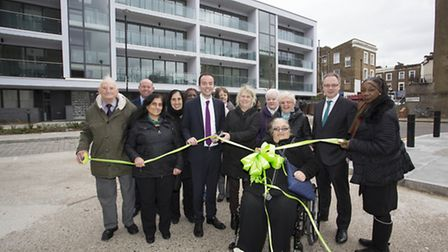 Incoming residents of Lyon House, pictured in the background, joined Cllr James Murray, sixth left,