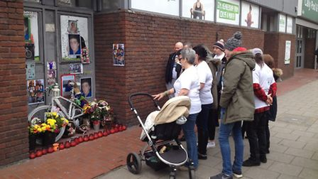 The family of Alan Cartwright pay their respects at his memorial outside Cally Pool, in Caledonian R
