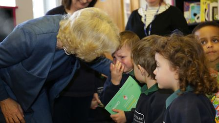 The Duchess of Cornwall puts a comforting arm around the shoulder of a nursery pupil from Sacred Hea
